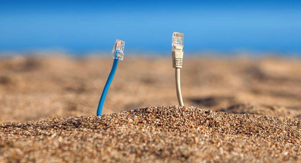 Deux câbles éthernet sortent du sable