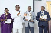 """Le ministre en charge de l'Industrie, Harouna KABORÉ (micro) a décerné des prix spéciaux aux hommes d'affaires Simone Zoundi (à gauche), Lazare Soré et Lassiné Diawara (à droite) lors de la """"Nuit du mérite""""."""
